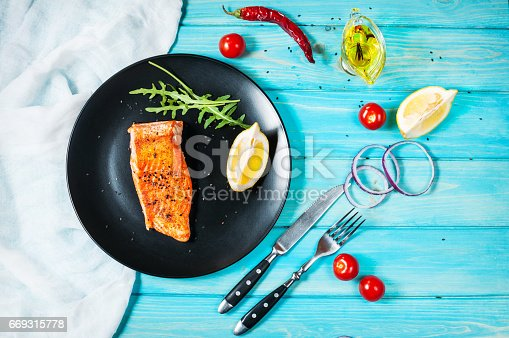 655794674istockphoto One piece of baked salmon with lemon 669315778