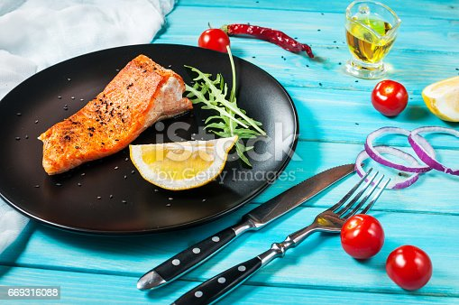 655794674istockphoto One piece of baked salmon with lemon 669316088