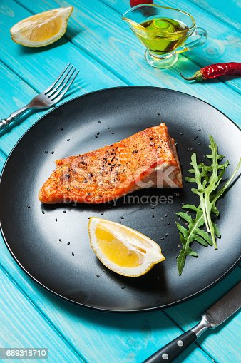 655794674istockphoto One piece of baked salmon with lemon 669318710