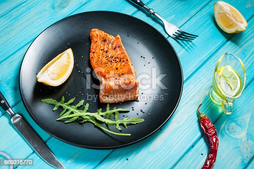 655794674istockphoto One piece of baked salmon with lemon 669318770