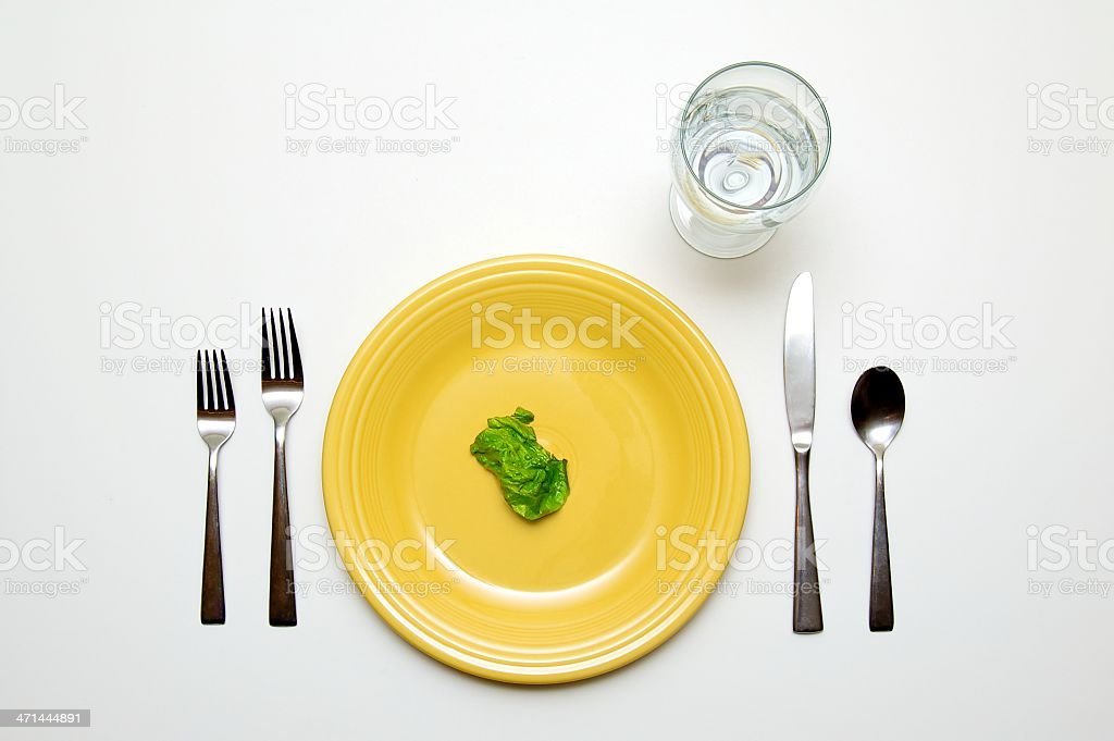 One piece of lettuce on a plate representing eating disorder stock photo