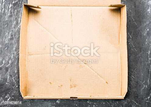 One piece of pizza in cardboard pizza box Top view of empty box with copy space on dark concrete background