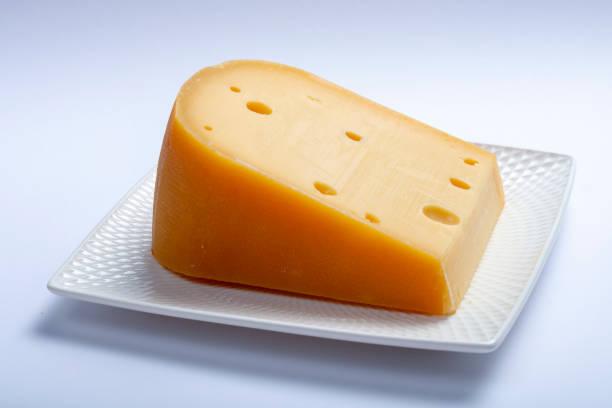 een stukje traditionele hollandse oude harde kaas gemaakt van koeienmelk - beemster stockfoto's en -beelden