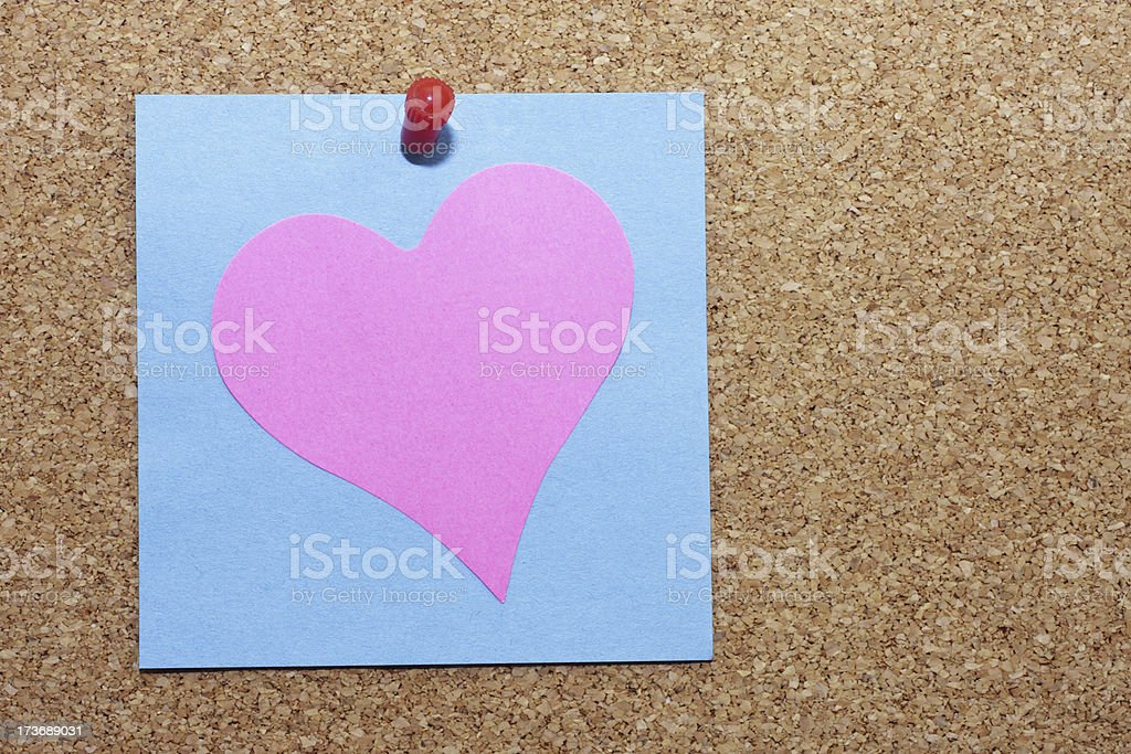 Pink Valentine's heart pinned with blue Post-It stickie notelet stock photo