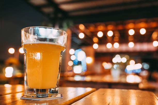 ein pint bier am tisch im restaurant mit textfreiraum auf weichzeichnen bokeh hintergrund. freudiges ereignis feiern, nachtleben party im pub oder alkoholische getränke werbung konzept - goldene bar stock-fotos und bilder
