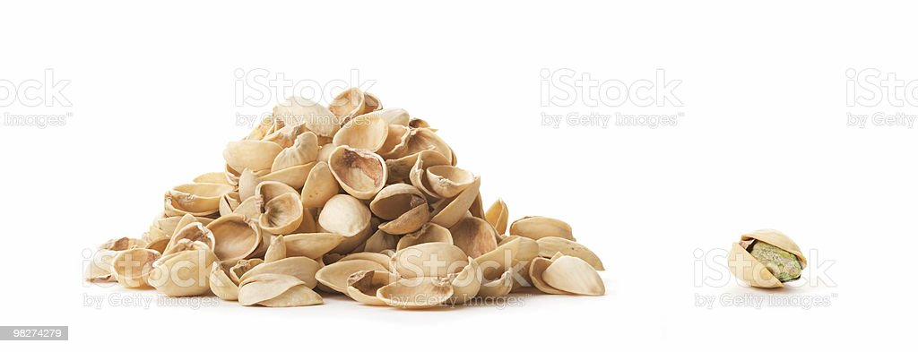 One Pistachio Beside Empty Shells royalty-free stock photo