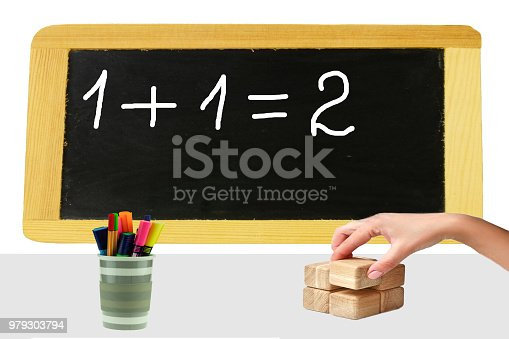 istock One plus one equal two are written on a blackboard and a womans hand take one block from a stack wooden blocks. Education concept. 979303794