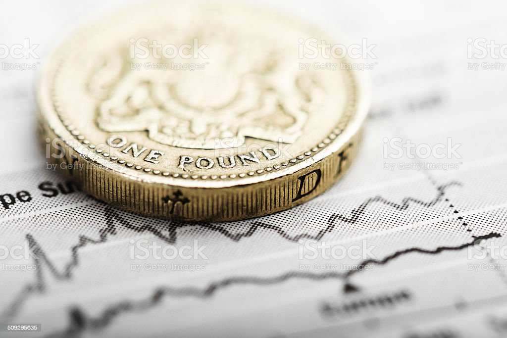 one pound coin on fluctuating graph stock photo