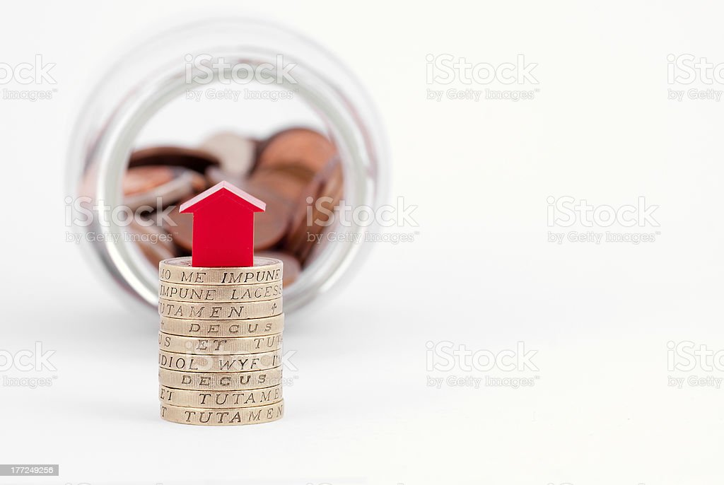 One Pound Coins and Red House royalty-free stock photo