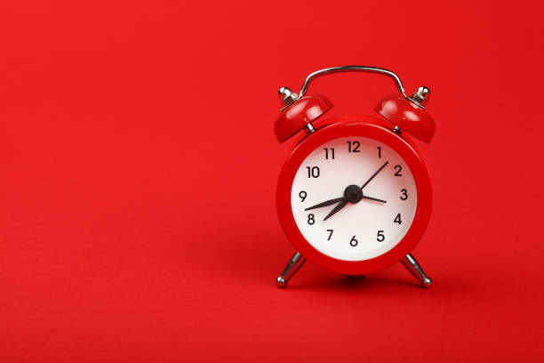 one red alarm clock over red background close up - alarm clock stock photos and pictures