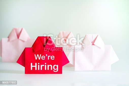1153648747istockphoto One Red among white origami shirt paper with We're Hiring message text , recruitment Human resource for the employee unique individuality and difference or leadership concept. 950577502