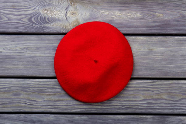 One red beret hat. One red beret hat. Top view, flat lay. Wooden desk surface background. beret stock pictures, royalty-free photos & images