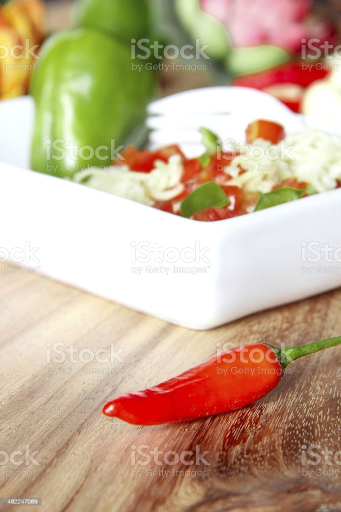 One red chili in front of salad plate stock photo