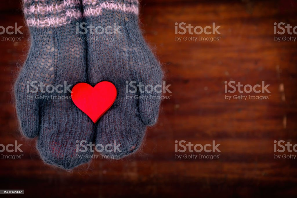 one red heart in hands stock photo