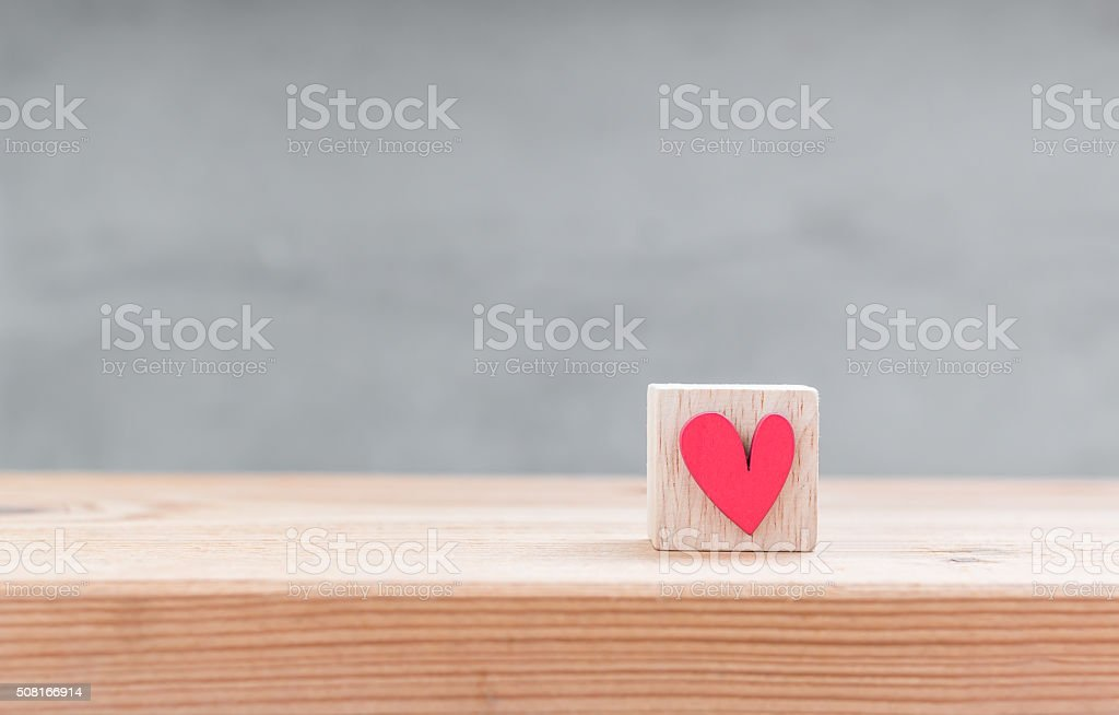One red heart shape in wood cube on wood table stock photo