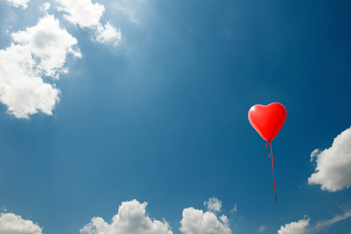 One red heart-shaped balloon floating in a blue sky with copy space.