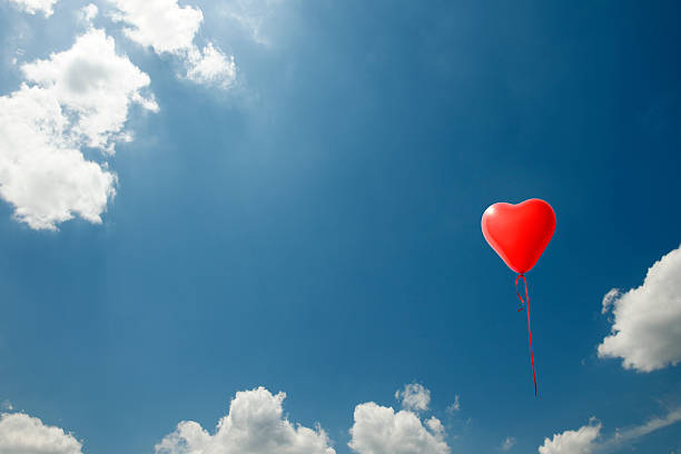 One red heart-shaped balloon floating in a blue sky stock photo