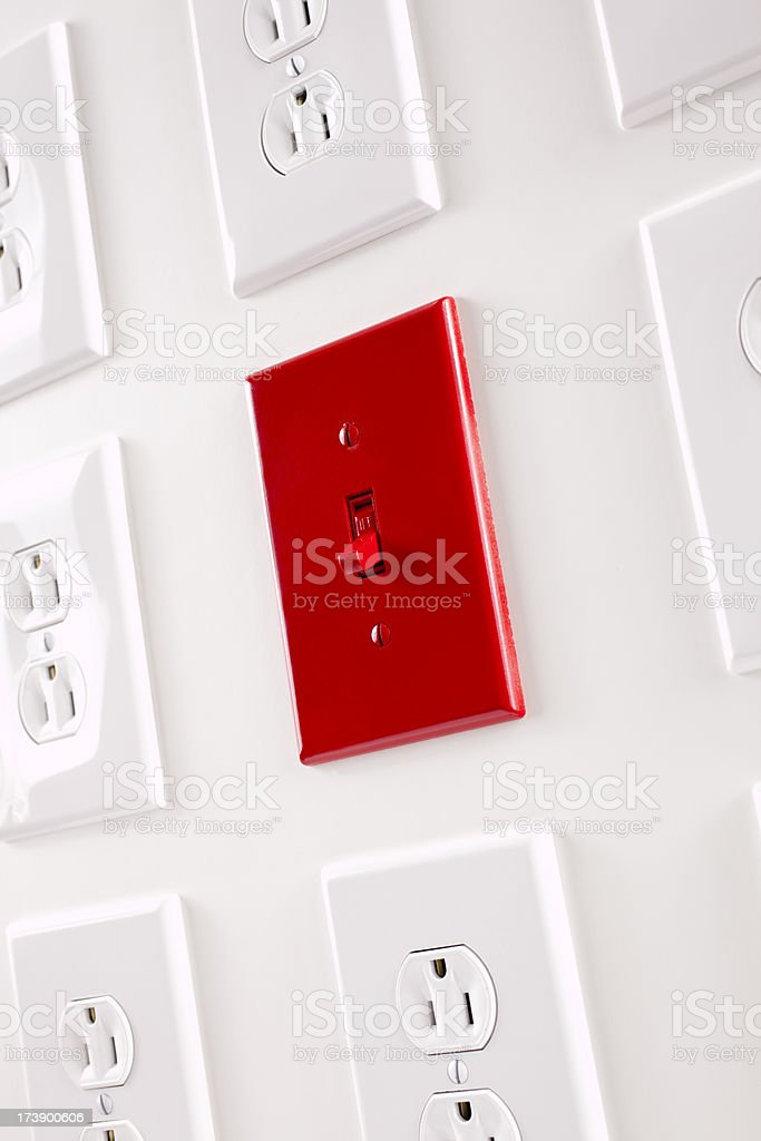 One red light switch among many white plug outlets royalty-free stock photo