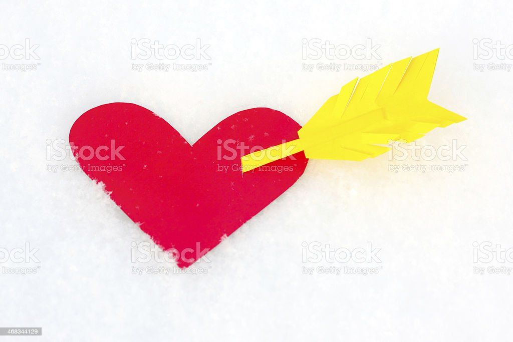 One red paper heart shape with arrow in the snow royalty-free stock photo