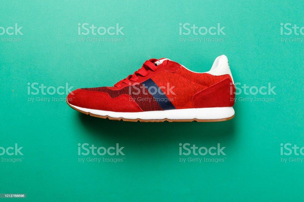 una zapatilla roja sobre un fondo de contraste brillante. foto de stock libre de derechos