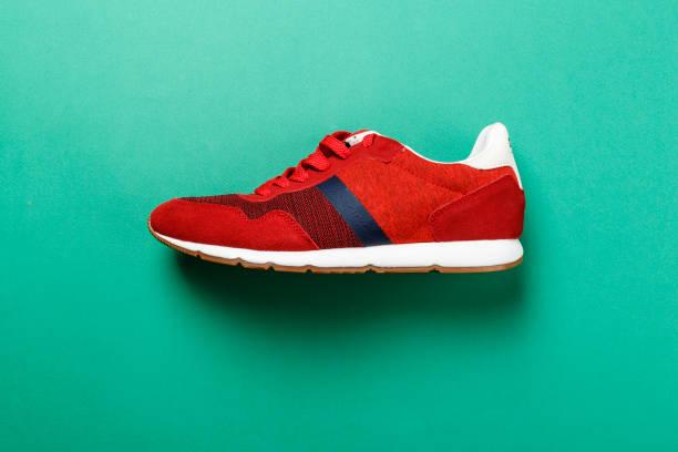 ein roter sneaker auf einem hellen, kontrastreichen hintergrund. - schuhe auf englisch stock-fotos und bilder
