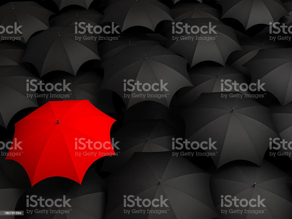 One red umbrella amongst several black umbrellas stock photo