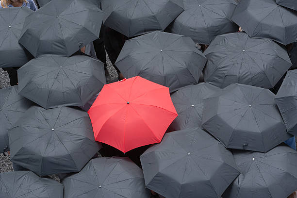 One red umbrella at center of multiple black umbrellas stock photo