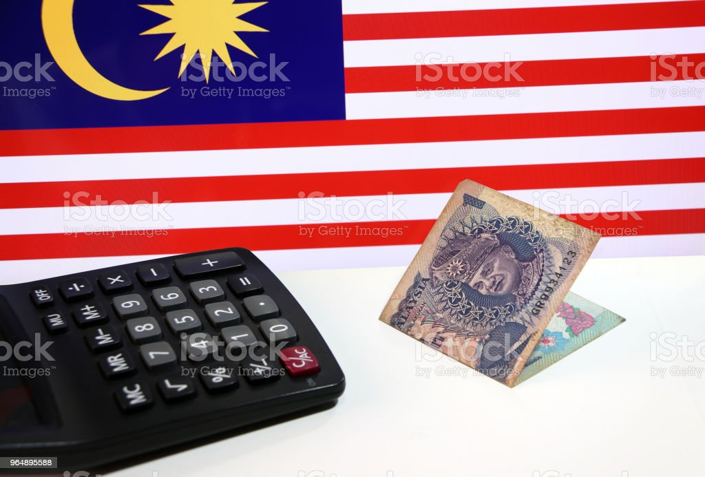 One ringgit banknote of Malaysia and calculator on the white floor with Malaysian nation flag background. royalty-free stock photo