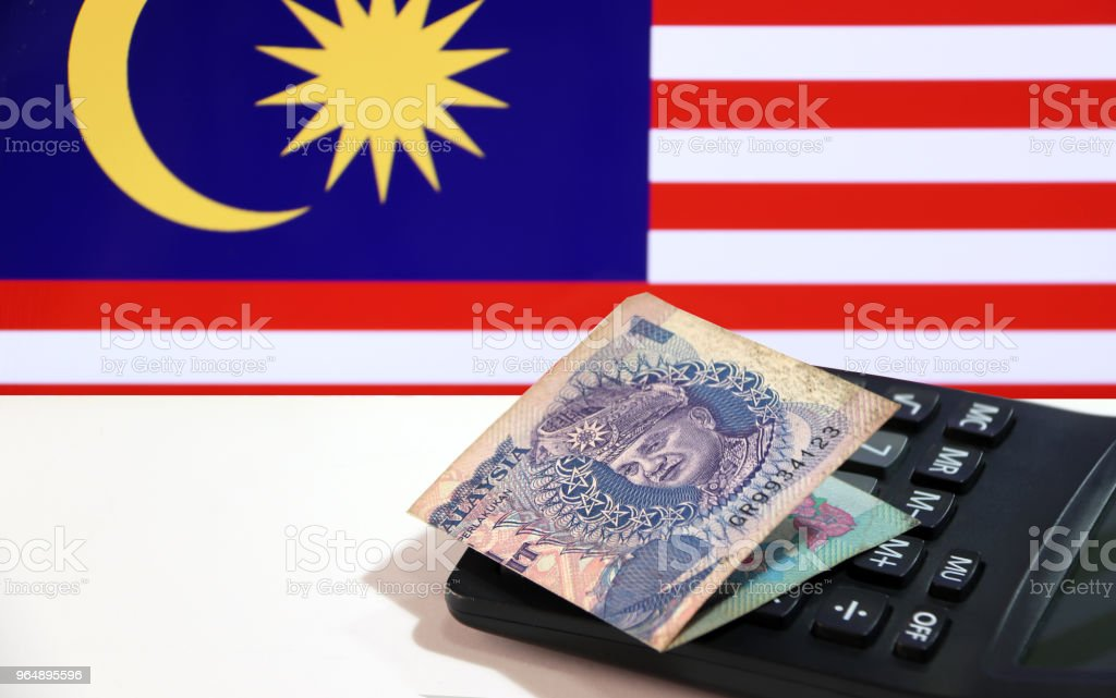 One ringgit banknote of Malaysia on calculator on the white floor with Malaysian nation flag background. royalty-free stock photo