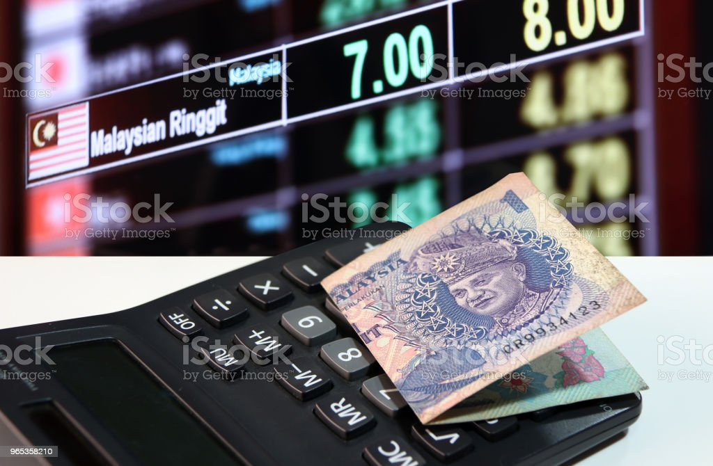 One ringgit banknote of Malaysia on calculator on the white floor with digital board of currency exchange money background. royalty-free stock photo