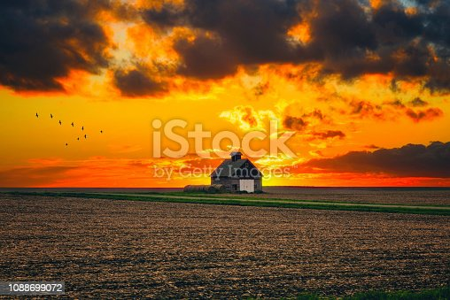 One rural barn in the middle of field landscape on the sunset and the stormy sky background.