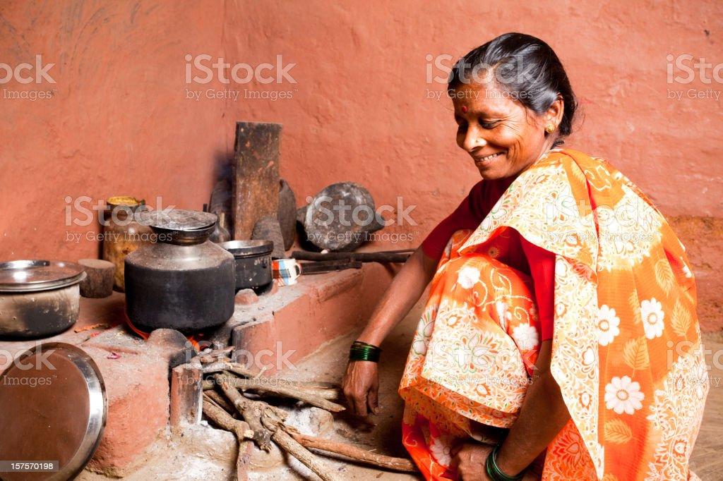 One Rural Indian Female Woman preparing food royalty-free stock photo