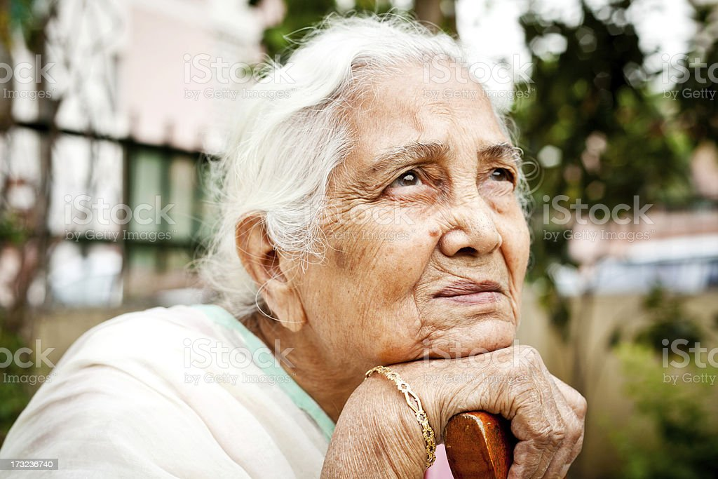 One sad pensive senior Indian woman looking up stock photo