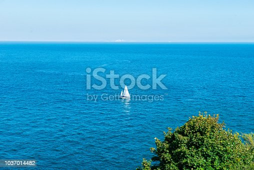 One Sailing yacht in the middle of brigh blue sea. Travel and active lifestyle concept. Selective focus. copy space