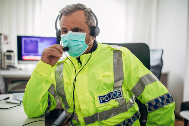 One senior British police officer with protective mask in the office stock photo