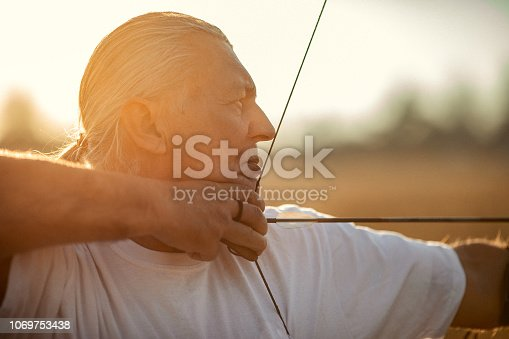 istock One senior man aiming with bow and arrow 1069753438
