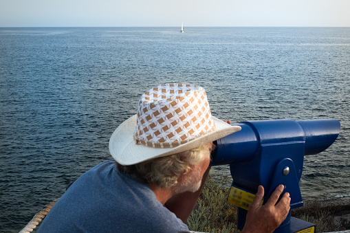 One senior man looking through the tourist telescope turned towards infinity. Seascape of the blue Atlantic ocean. Coin-operated binoculars for landscape exploration