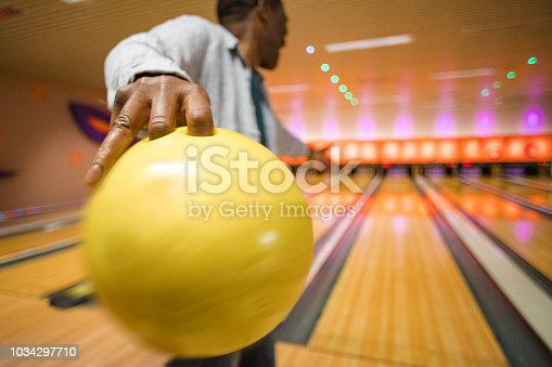 Rear, close-up shot of a senior man about to throw a bowling ball down the bowling alley.