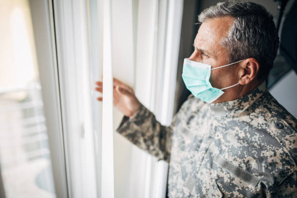One senior military soldier with protective mask standing in the office stock photo