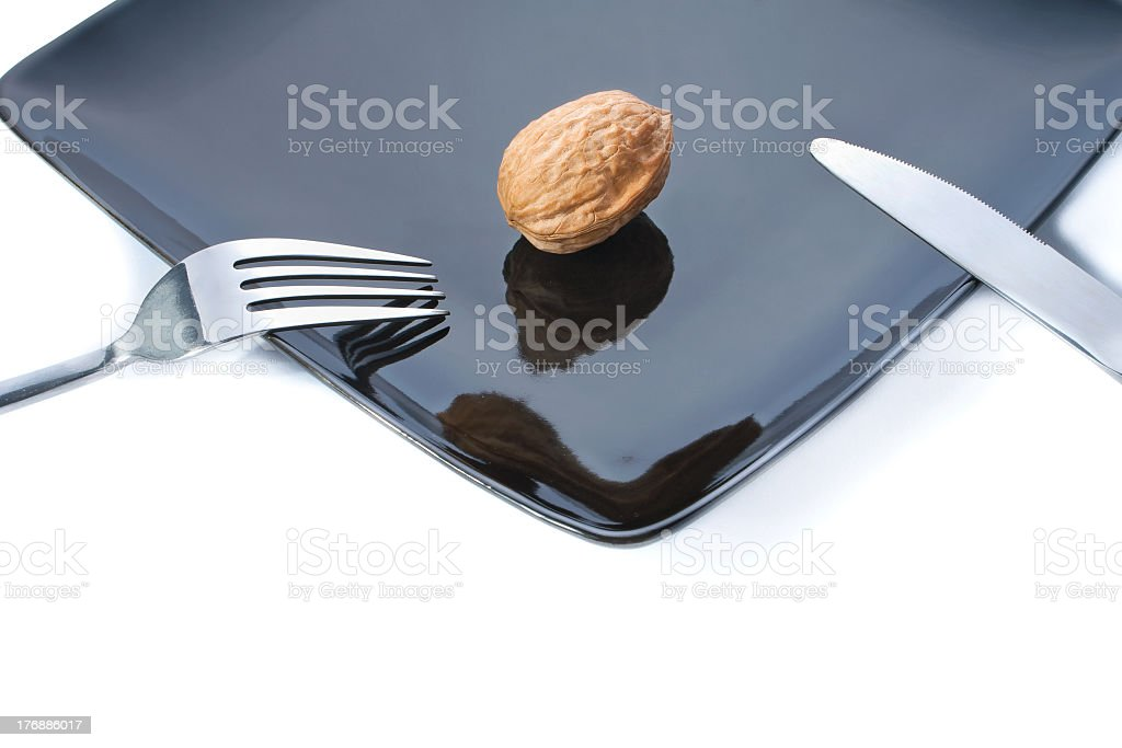 One shelled walnut on a plate with utensils royalty-free stock photo