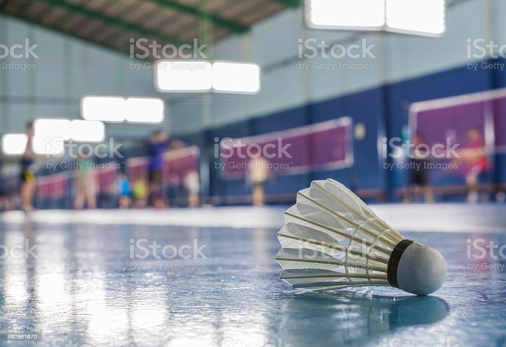 One shuttlecock on the ground in the Badminton court stock photo