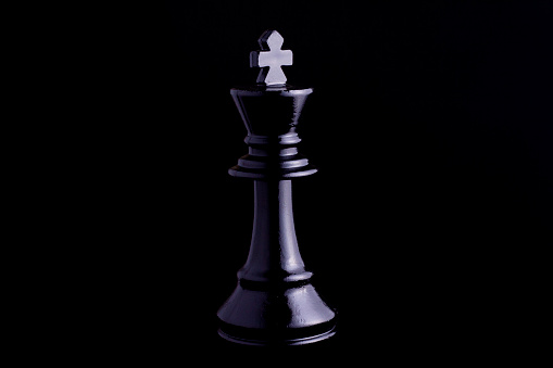 one side light on Black king chess piece in black background