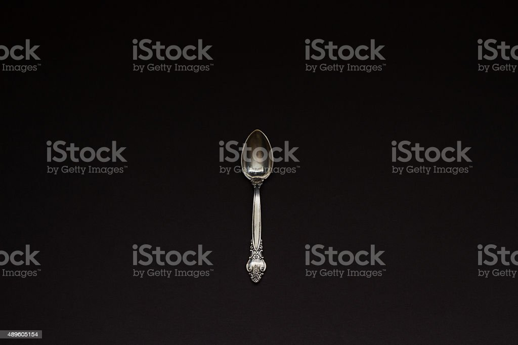 One silver spoon on black background stock photo
