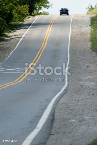A single car is cresting a hill on a two-lane rural highway