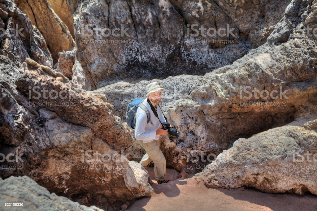 One smiling backpacker goes down path between rocks, with camera. stock photo