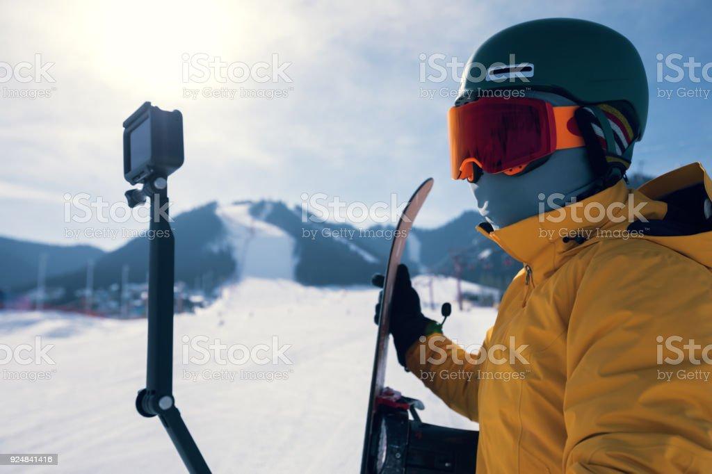 one snowboarder use action camera taking selfie on winter ski resort piste – zdjęcie