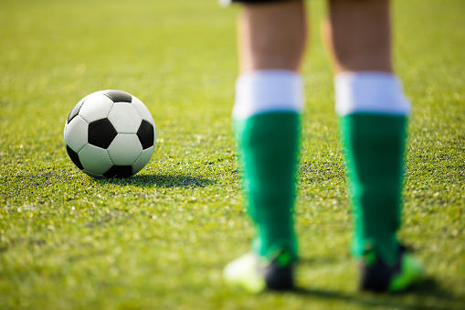 One soccer football player standing next to ball ready to kick. Legs of junior level football player an classic soccer ball