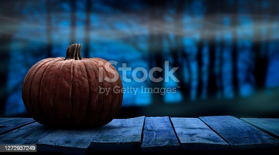One spooky halloween pumpkin blank template on a wooden bench with a misty forest night background with space for product placement.