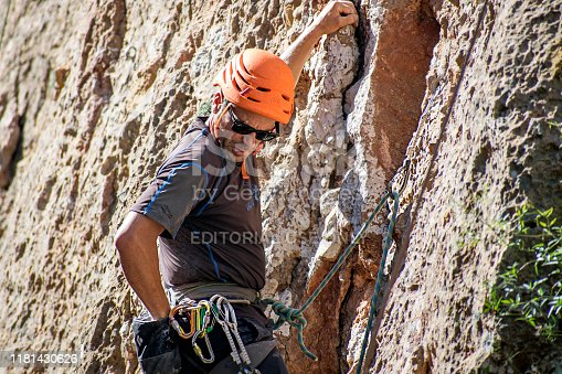 Murcia, Spain, September 27, 2019. One sportsman mountain climbing for fun in el Valle, Murcia. Physical activity in the countryside. Risky sports. Mountain climb or climbing is a dangerous exercise that needs safety equipment.