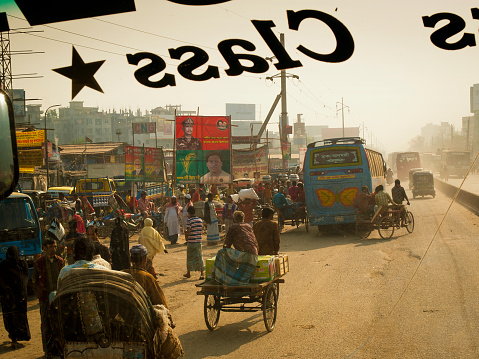 Dhaka, Bangladesh - February 2, 2012: Chaotic street full of rickshaw and people selling goods in front of busy bazaar, with obsolete residential buildings in Dhaka city in Bangladesh.